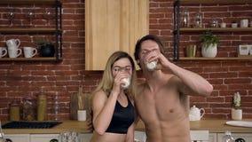 Het portret van een jong Kaukasisch paar drinkt gezonde melk thuis in de keuken Gezonde drank, dieet, gezonde levensstijl stock videobeelden