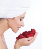 Het portret van een jonge donkerbruine holding nam bloemblaadjes toe Stock Foto