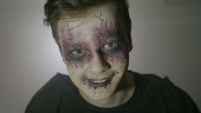 Het portret van een jonge mens van de psychopaatzombie met vreemde ogen en gezichtsverf die angstaanjagend Halloween doen beweegt stock videobeelden