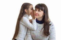 Het portret van een jonge moeder en een dochter die de geheimen op het oogje plaatst is geïsoleerd op een witte achtergrond royalty-vrije stock fotografie