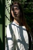 Het portret van een jonge vrouw, de schaduw van het rooster valt op Th stock fotografie