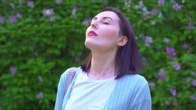 Het portret van een jonge vrouw gaat haar medisch masker van start en ademt diep in de lucht tegen de achtergrond van bloemen stock video