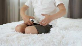 Het portret van een jongen, zit op een bed en speelt met een smartphone Moderne ontwikkeling, onderwijs van kleuterschool stock videobeelden