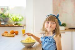 Het portret van een klein meisje eet een spaghetti en dwazen royalty-vrije stock afbeeldingen