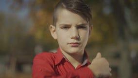 Het portret van een kleine jongen verbetert haar met zijn hand en het leuke glimlachen stock videobeelden