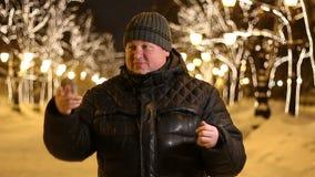 Het portret van een knappe mens in zwarte nodigt bij nacht in de straat van de de winterstad uit stock videobeelden