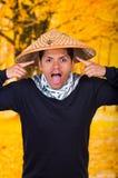 Het portret van een knappe Spaanse jonge bedrijfskerel die een Aziatische kegelhoed dragen die een dwaas gezicht doen en neemt Stock Afbeeldingen