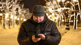 Het portret van een knappe vette mens in zwarte gebruikt zijn telefoon bij nacht in de straat van de de winterstad stock video