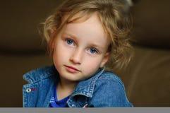 Het portret van een krullend blauw-eyed meisje met een rust ziet eruit Zij draagt een denimvest Royalty-vrije Stock Foto