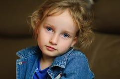 Het portret van een krullend blauw-eyed meisje met een rust ziet eruit Zij draagt een denimvest Stock Afbeelding