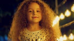 Het portret van een leuk Europees krullend-haired meisje een kind bekijkt de camera zoet glimlachend tegen de achtergrond stock videobeelden