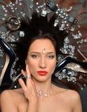 Het portret van een luxueus donkerbruin meisje ligt in een placer van diamantenjuwelen, luxetoebehoren royalty-vrije stock afbeelding