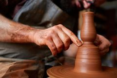 Het portret van een mannelijke pottenbakker in schortvormen werpt van klei, selectieve nadruk, close-up royalty-vrije stock foto