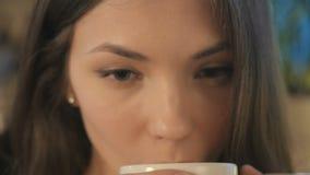 Het portret van een meisje drinkt een koffie stock video