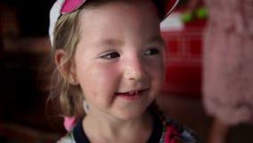 Het portret van een meisje in een GLB drie jaar het oude glimlachen en iets toont langzame motie stock footage