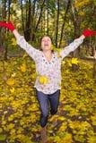 Het portret van een meisje werpt zich esdoornbladeren Royalty-vrije Stock Afbeelding