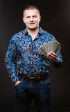 Het portret van een mens in een overhemd en jeans houdt heel wat honderd dollarsrekeningen De kerel houdt een salaris, geld royalty-vrije stock foto