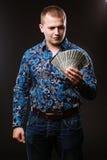 Het portret van een mens in een overhemd en jeans houdt heel wat honderd dollarsrekeningen De kerel houdt een salaris, geld royalty-vrije stock foto's