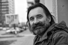 Het portret van een mens, kijkt over zijn schouder met een glimlach Stock Foto's