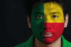 Het portret van een mens met de vlag van Benin schilderde op zijn gezicht op zwarte achtergrond royalty-vrije stock foto's