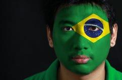 Het portret van een mens met de vlag van Brazilië schilderde op zijn gezicht stock afbeeldingen