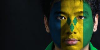 Het portret van een mens met de vlag van de Heilige Vincent schilderde op zijn gezicht op zwarte achtergrond stock afbeelding