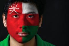 Het portret van een mens met de vlag van Oman schilderde op zijn gezicht op zwarte achtergrond royalty-vrije stock afbeelding