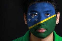 Het portret van een mens met de vlag van Solomon Islands schilderde op zijn gezicht op zwarte achtergrond royalty-vrije stock afbeelding
