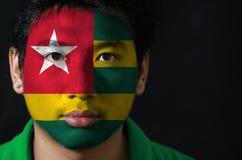 Het portret van een mens met de vlag van Togo schilderde op zijn gezicht op zwarte achtergrond royalty-vrije stock afbeeldingen