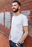 Het portret van een modieuze en positieve Kerel, in een witte lege t-shirt, tegen de oranje bakstenen muur, kan voor reclame, tek stock afbeelding