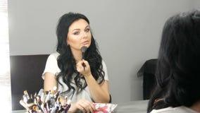 Het portret van een mooi blauw-eyed vrouwenmodel met lange zwarte haarzitting voor spiegel en past make-up aan gebruikend a stock videobeelden