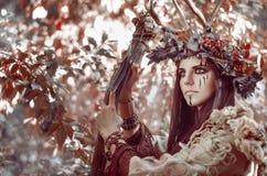 Het portret van een mooi brunette met een geschilderd gezicht, klerenmedicijnman, een bloemenkroon op haar hoofd en hoornen, die  royalty-vrije stock fotografie