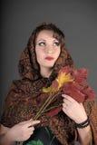 Het portret van een mooi donkerharige met een sjaal op haar hoofd en herfst gaat weg Royalty-vrije Stock Afbeelding