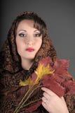 Het portret van een mooi donkerharige met een sjaal op haar hoofd en herfst gaat weg Stock Afbeelding