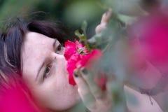 Het portret van een mooi jong individueel, zonderling donkerharige, haar neus plakte diep in geurige rode rozen stock foto