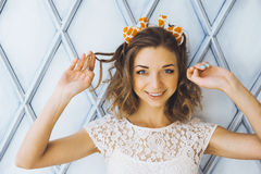 Het portret van een mooi jong zoet meisje met het charmeren glimlacht en hoornen op het hoofd van een en giraf die stellen glimla Stock Afbeeldingen