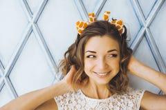 Het portret van een mooi jong zoet meisje met het charmeren glimlacht en hoornen op het hoofd van een en giraf die stellen glimla Stock Foto