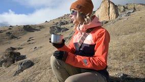 Het portret van een mooi meisje in een hoed en zonnebril met een mok in haar handen drinkt koffie of thee terwijl het zitten stock video