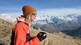 Het portret van een mooi meisje in een hoed en zonnebril met een mok in haar handen drinkt koffie of thee terwijl het zitten stock videobeelden