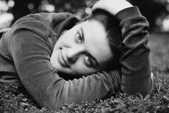 Het portret van een mooi meisje met kort haar en groene ogen ligt op het gras die, die en de camera glimlachen bekijken stock afbeelding
