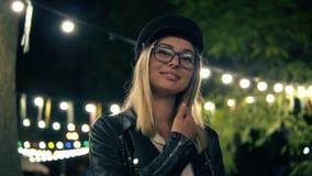 Het portret van een mooi meisje in modieuze hoed, manierglazen en een zwart leerjasje loopt in het nachtpark licht stock video