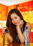 Het portret van een mooie gedronken vrouw die haar stellen dient haar kin in, met een fles van bier en water en het houden van ee stock fotografie