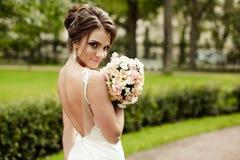 Het portret van een mooie gelukkige donkerbruine bruid in holding van de huwelijks de witte kleding dient boeket in openlucht van Royalty-vrije Stock Foto's