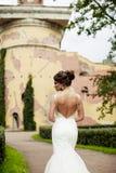 Het portret van een mooie gelukkige donkerbruine bruid in holding van de huwelijks de witte kleding dient boeket in openlucht van Stock Fotografie