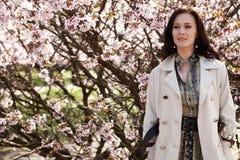 Het portret van een mooie jonge vrouw op een achtergrond van roze kers komt in de lente, levensstijlconcept tot bloei stock afbeeldingen