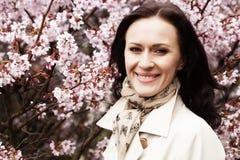 Het portret van een mooie jonge vrouw op een achtergrond van roze kers komt in de lente tot bloei, stock foto's