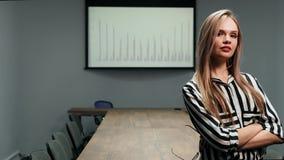 Het portret van een sexy blonde bedrijfsvrouw in bureau kleedt status in het bureau tegen een grote lijst en grafieken stock footage