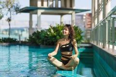 Het portret van een sexy meditatie Kaukasische vrouw in een zwempakzitting in lotusbloem stelt op de rand van een dakpool met gro stock afbeeldingen