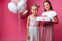 Het portret van een tiener op een roze achtergrond, met giften, verjaardagsconcept, één geeft een ander meisje een gift royalty-vrije stock afbeelding