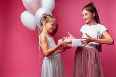 Het portret van een tiener op een roze achtergrond, met giften, verjaardagsconcept, één geeft een ander meisje een gift royalty-vrije stock foto's